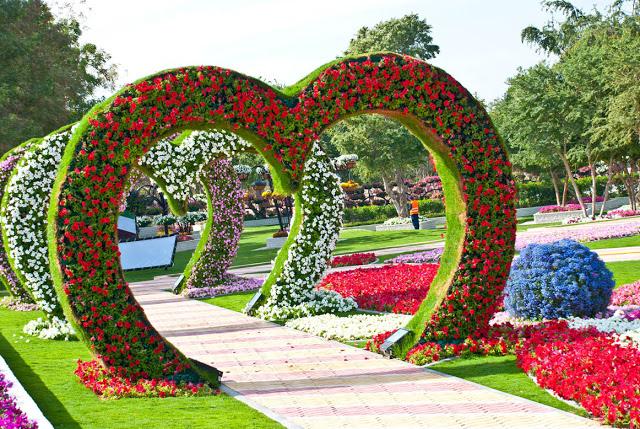 حديقة عامة وفيها مسار عليه مجسمات على شكل قلوب ومغطاه بالزهور بحيث يمكن للزوار المرور من تحتها